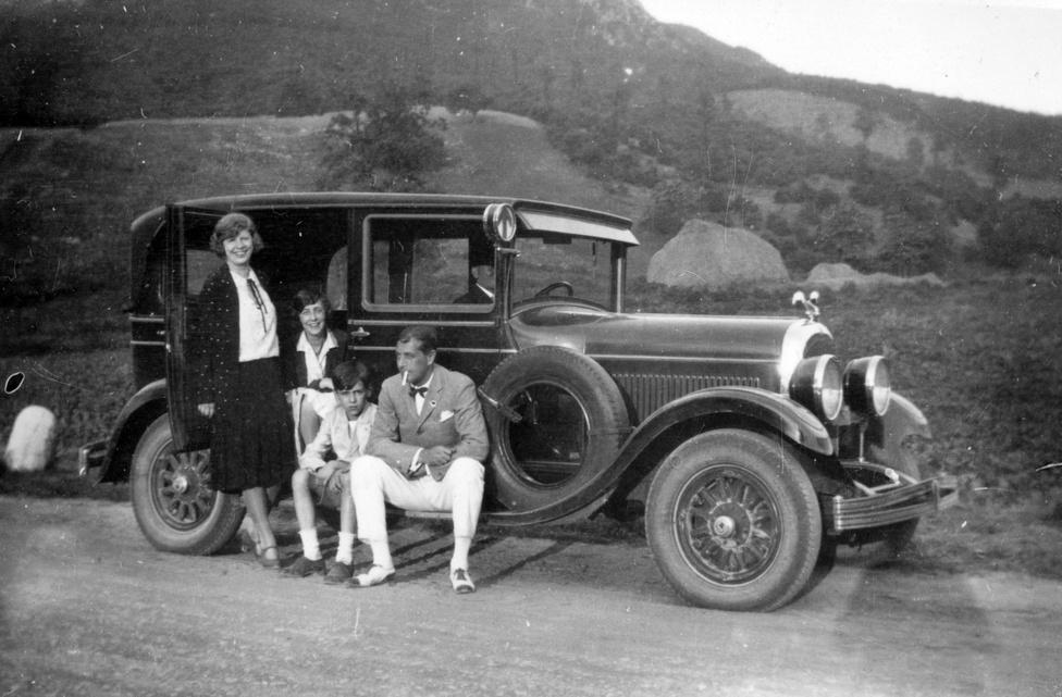1929. A lestrapált apuka passzív dohányzásnak teszi ki két gyermekét és a felesége őnagyságát. A férfi borús tekintete annak szól, hogy Magyarország eladósodási folyamata már három éve tart, az államháztartás deficites, rövid lejáratú hiteleket felvenni képtelenség. Itt még nem tudja, hogy néhány hónap múlva jön a fekete csütörtök, és kezdetét veszi a részvénypiaci recesszió. Az élet apró örömének tűnik ezek után, hogy ő még vígan dohányozhatott Chryslerében a két gyermeke jelenlétében is, a 2010-es években ugyanis ezt egy sor országban tiltják Ausztráliától Dél-Afrikáig, Bahreintől  Ciprusig.
