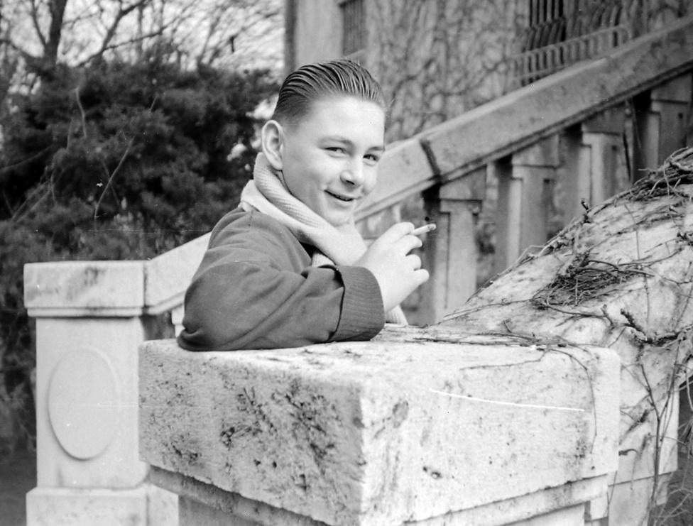 1957. Puskás Öcsi-frizurával pózol egy évvel a forradalom után ez a taknyos gyerek, aki ma, ha bele nem halt azóta a dohányzás ártalmaiba, jó 70 éves lehet. Nem okozott gondot cigarettát vásárolni, hiszen akkoriban még nem voltak nemzeti dohányboltok, ahová a 18 éven aluliak be nem tehetik a lábukat, és a trafikokban sem kértek személyi igazolványt dohányáru  vásárlásához.