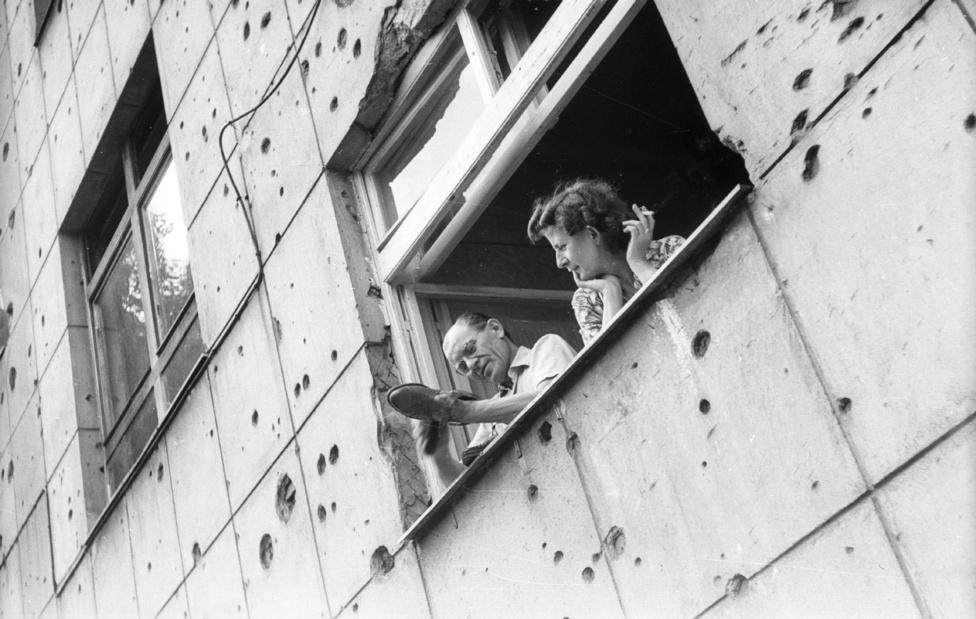 1964. Budapest, Gizella út 33. Az épület ma is megvan, és nincs sokkal jobb állapotban, de a golyónyomokat már eltüntették. Az ablakon kihajoló pár hölgy tagja talán az abban az évben megjelent Velencét szívta, az első king size (84 mm) méretű magyar cigarettát. Igazi női cigaretta volt, mivel filtere rúzsvörös volt. Mondjuk, nem volt olcsó, nyolc forintba került.