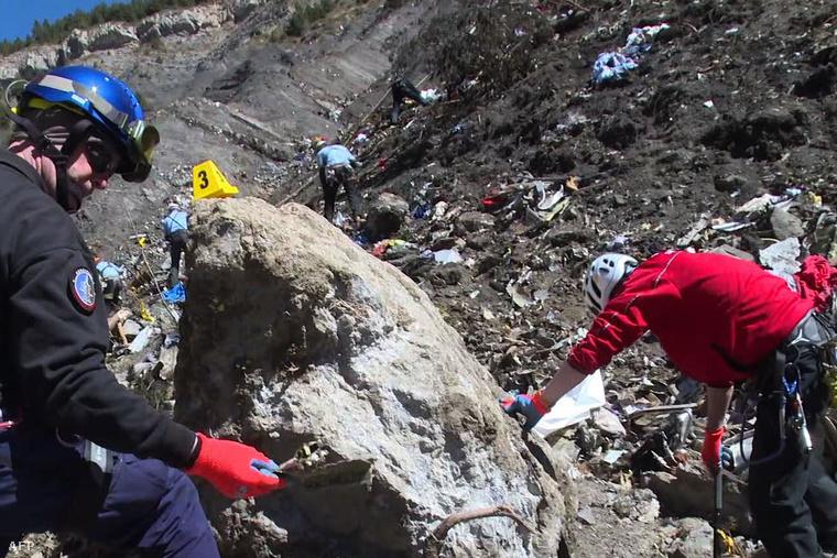 Mentőcsapatok dolgoznak a hegyen a gép roncsai között.