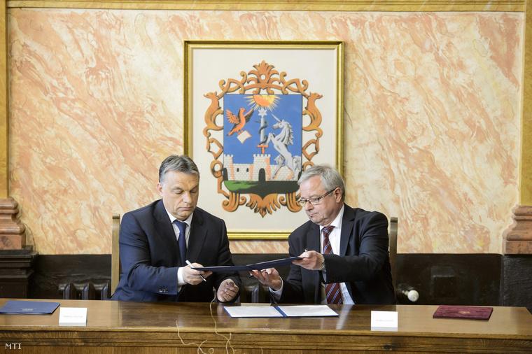Orbán Viktor miniszterelnök (b) és Habis László polgármester fejlesztési megállapodást ír alá az egri városháza dísztermében