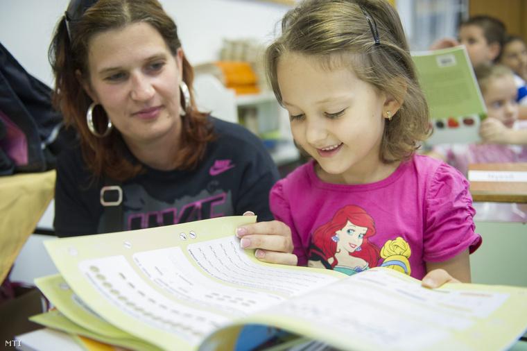 Elsős diák lapoz egy tankönyvet édesanyjával az Orosházi Vörösmarty Mihály Általános Iskola 1.a osztályában 2014. szeptember 1-jén.