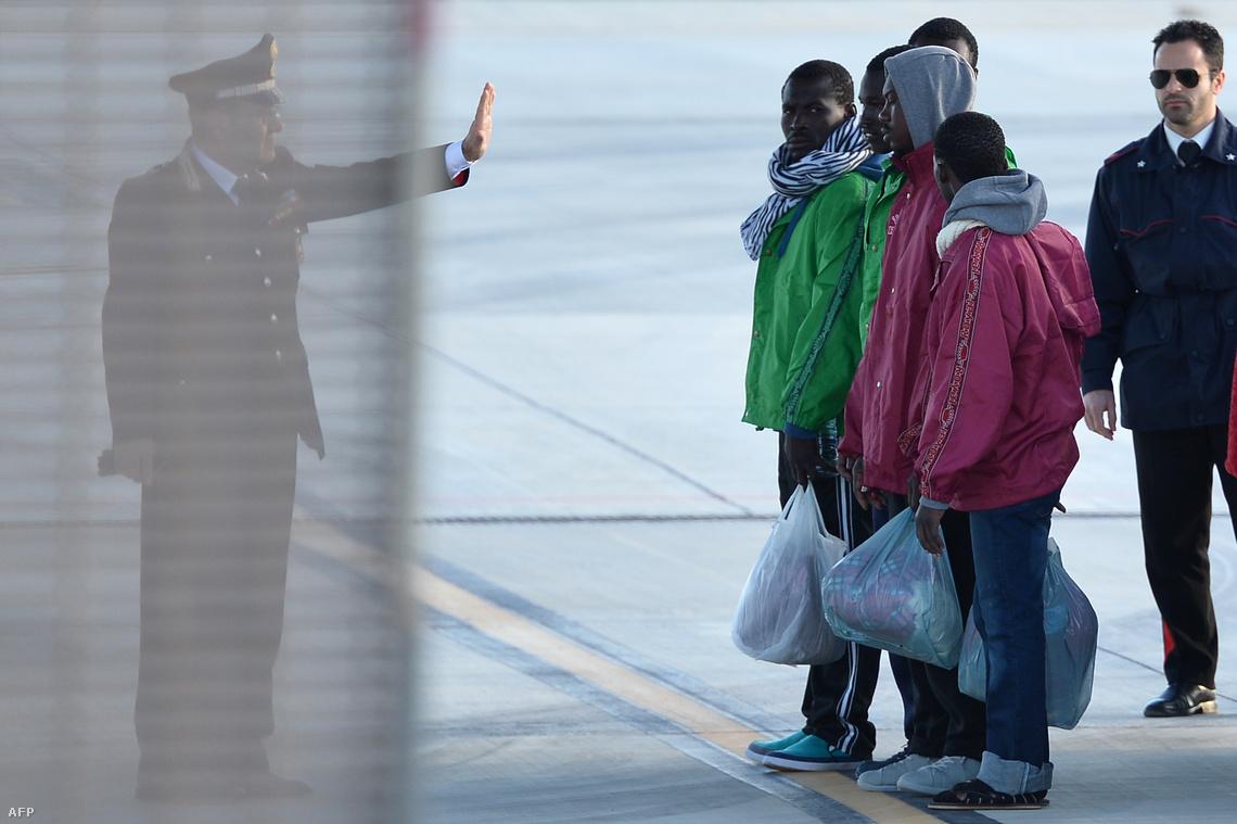 Egy olasz tiszt és az ideiglenes táborukat elhagyó menekültek Lampedusa repülőterén. Mivel az apró sziget kapacitásai végesek, a befogadott menekülteket innen az olasz szárazföldre szállítják.