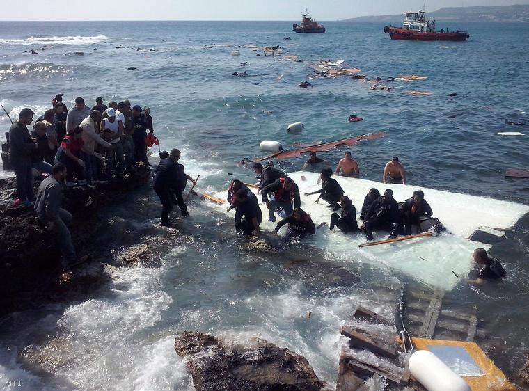 Illegális bevándorlók a Rodoszon fekvő Zefirosz tengerpartján 2015. április 20-án miután zátonyra futott az őket szállító hajó. A mintegy 200 menekültnek sikerült sértetlenül partot érni.