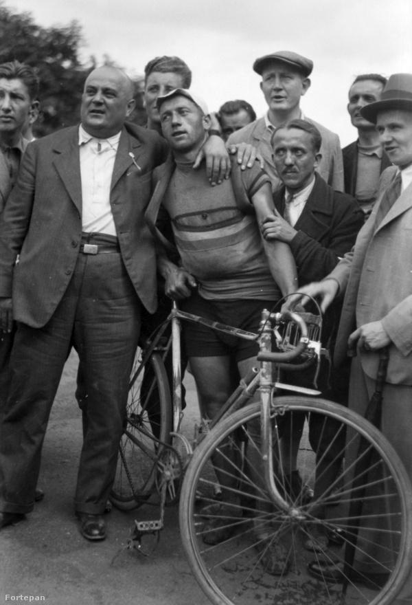 Kerékpározás. Soha nem szereztünk érmet. A kép 1933-ban készült, egy feltehetően kissé kapatos szurkoló vagy támogató ölelget egy fáradt versenyzőt, aki szemmel láthatóan szívesen lenne valahol máshol. A korszak nagy sztárjai különben az olaszok voltak, az 1932-es Los Angeles-i olimpián három aranyérmet szereztek, Attilio Pavesi egymaga kettőt. Pavesi különben 100 éves korában, 2011-ben halt meg a világ legidősebb olimpiai bajnokaként. Halála után ez a cím a magyar pólós Tarics Sándorra szállt.                                                  1933.