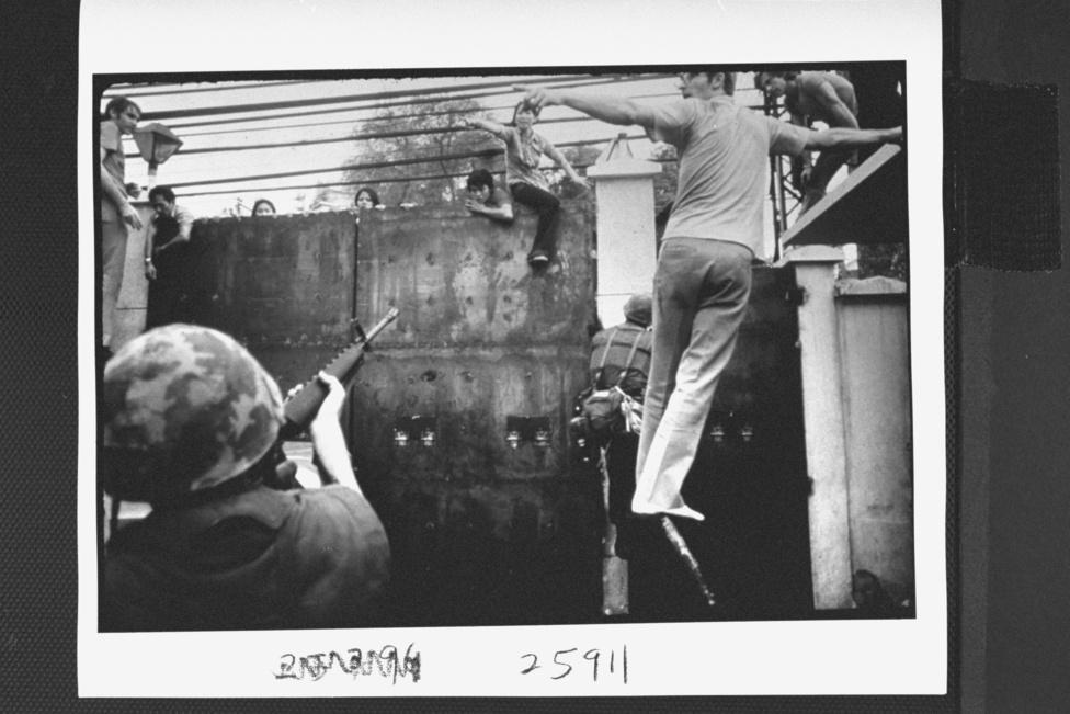 Egy követséget védő tengerészgyalogos puskát szegez egy vietnaminak, aki elszánta magát, hogy vagy meghal, vagy amerikai lesz.