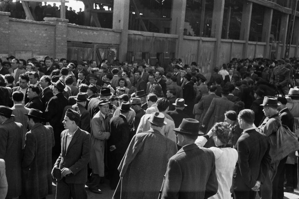 """""""Jó, hogy nem találják ki a vénaszkennert a nagy okosok, már így is alig lehet bejutni a stadionba. Vagy hogy nem változtatják meg a nevünket Édoszra vagy Kinizsire, csak hogy elvegyék a kedvünket, hahaha."""" Bejutásra váró tömeg a Fradi régi, falelátós stadionjában 1949-ben. Az 1948-49-es bajnokságot a Ferencváros 140 rúgott góllal nyerte 11 ponttal megelőzve a második helyezett MTK-t. A gólkirály a fradista Deák Ferenc lett 59 góllal."""