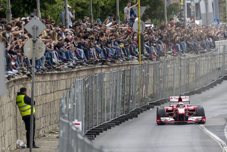 Kimi Räikkönen a Forma-1-es Ferrari finn pilótája halad a Várkert Bazár előtt.