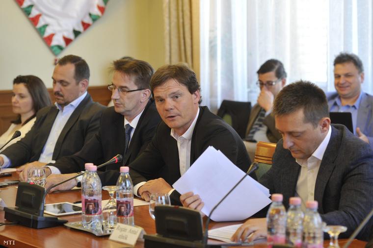 Bánki Erik, az Országgyűlés gazdasági bizottságának fideszes alelnöke (j2) kérdést tesz fel a testület ülésén, amelyen Windisch László, a Magyar Nemzeti Bank (MNB) alelnöke tartott tájékoztatót a Parlamentben 2015. május 12-én. Az ülésen az MNB-alelnök elmondta, hogy a bankok a mostani elszámolás során 744,4 milliárd forintot fizettek vissza devizahiteles ügyfeleiknek. Jobbról Rogán Antal, a bizottság fideszes elnöke, balról Völner Pál (b3) és Mengyi Roland (b2), a testület fideszes alelnökei.