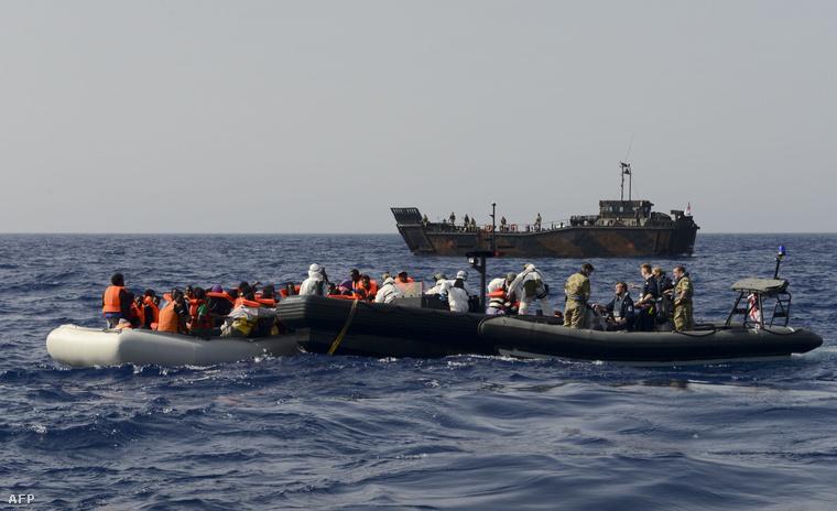A brit haditengerészet katonái csónakon hánykolódó menekülteket mentenek ki a Földközi tengerből.