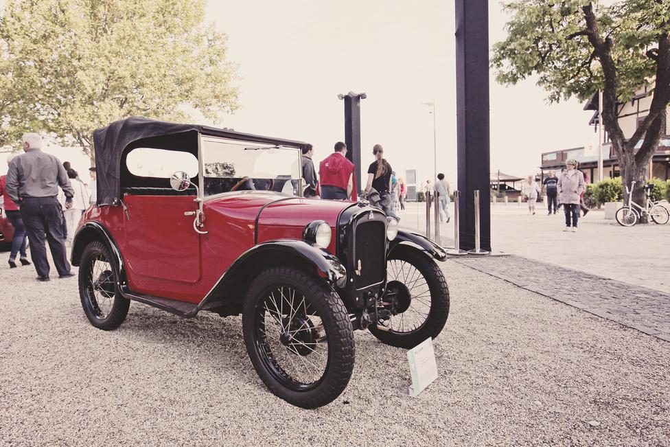 A brit Austin 1922-ben kezdte el gyártani a 7-est, amely hamarosan Európa első népautójává vált. Több gyárnak is eladták a licencét, többek között 1927-tól a német Automobilwerk Eisenachnak is, ahol Dixi 3/15 néven készült, bal oldali kormánnyal. Majd amikor az eredetileg repülögép-, majd motorkerékpár-gyártó BMW egy évvel később megvette a gyárat, átvették a Dixi gyártásának jogait is, megteremtve ezzel az első BMW autót.
