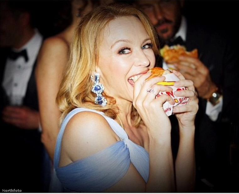 Kylie Minogue egy burgerbe harap éppen bele.